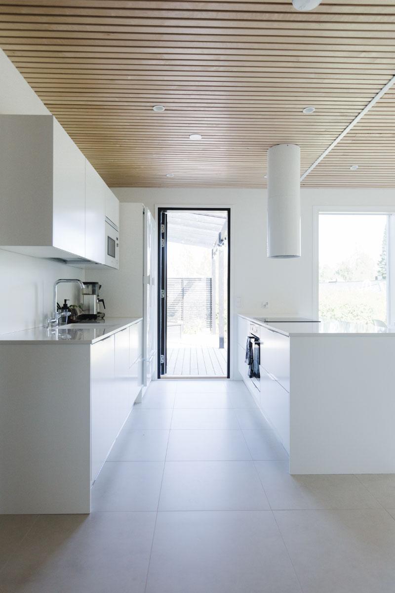 Omakotitalon valkoinen keittiö saarekkeella ja valkoisella liesituulettimella