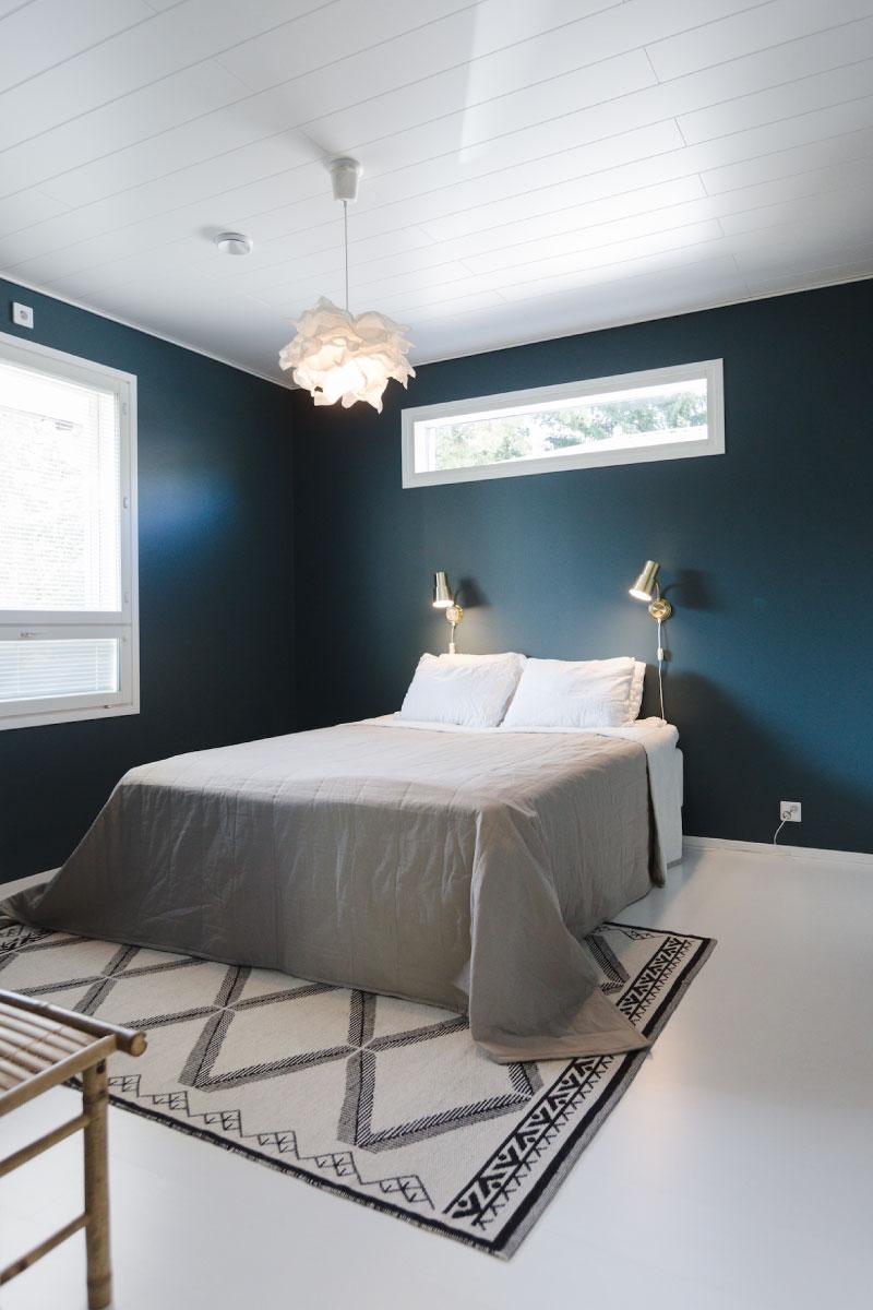 Omakotitalon meren tummalla tehosteseinällä varustettu makuuhuone jonka keskellä on parisänky.