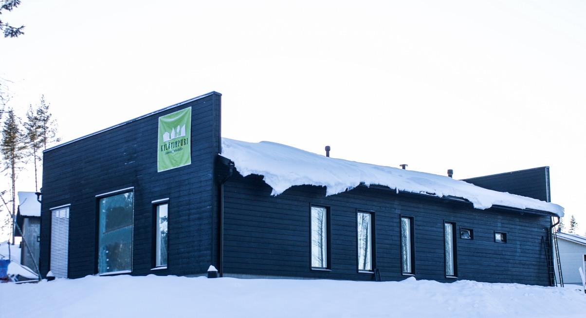 Kylätimpureiden rakentama yksikerroksisen omakotitalon musta julkisivu talvella