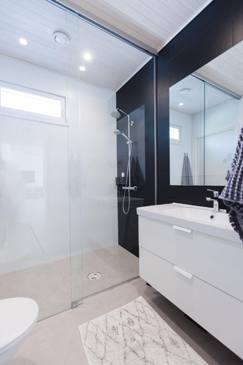 Omakotitalon valkoinen wc-kylpyhuone jossa yhdellä seinällä musta tehostemaali.