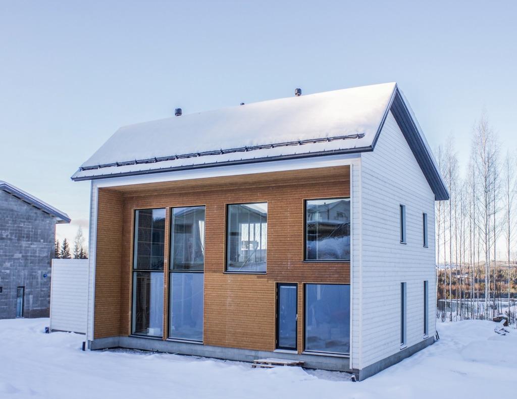 Uusi kaksikerroksinen omakotitalo ulkoa kuvattuna talvella